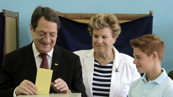 President Nicos Anastasiades, with his wife Andri and their grandson Andi, casts his ballot (AP)