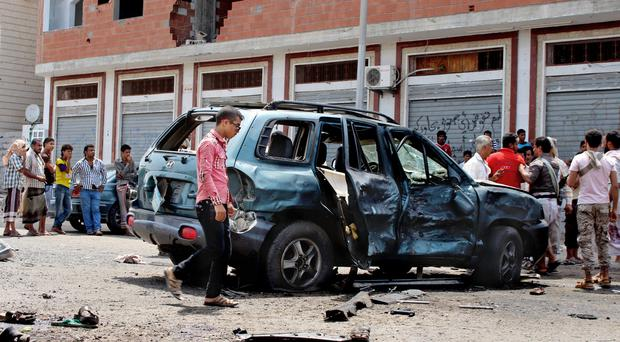 People gather at the scene after a pair of suicide bombings attack in the city of Aden in Yemen. (AP)