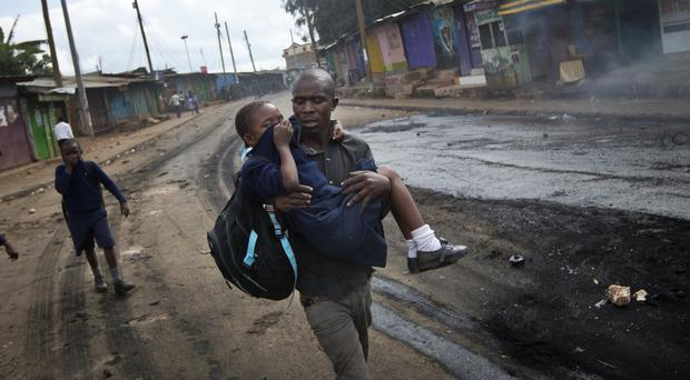 A man carries a schoolgirl overcome by tear gas to safety in Nairobi (AP)