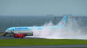 White smoke rises from an engine of a Korean Air jet as firefighters battle an apparent engine fire on the tarmac at Haneda Airport in Tokyo (Hiroshi Miyamoto/Kyodo News/AP)
