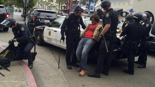 A man is taken into custody by police after a rally for Republican presidential candidate Donald Trump in San Diego (AP)