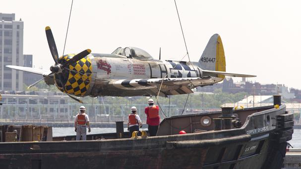 The vintage P-47 Thunderbolt aircraft being placed on a heliport pier after it was removed from the Hudson River (AP)