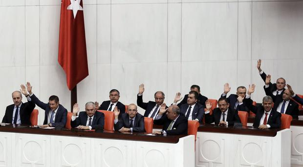 New Turkish Prime Minister Binali Yildirim (third from left) and his ministers raise their hands during a vote of confidence for his cabinet at the parliament in Ankara (AP)