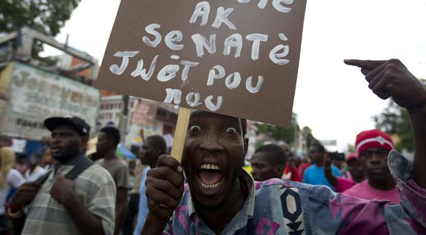 A supporter of presidential candidate Jovenel Moise holds up a sign with a message that reads in Creole