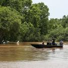 Two people pilot a boat through the flooded Brazos River in Rosenberg, Texas (Houston Chronicle/AP)