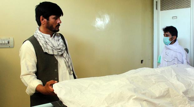 An Afghan man stands over the body of a victim of a Taliban attack on the road from Kabul to Kunduz on Tuesday (AP)