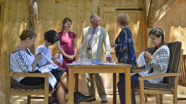 Charles listens to a trainer at a traditional sewing class in the Transylvanian village of Viscri, Romania (AP)