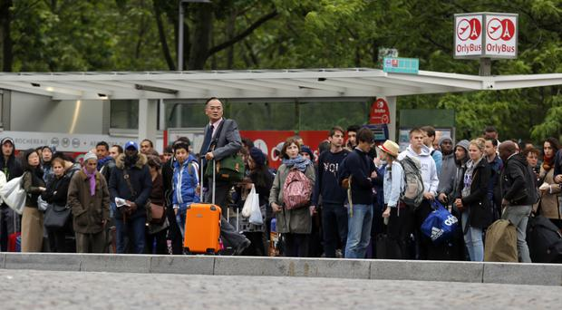 Commuters wait for a bus to Orly Airport during a railway strike in Paris (AP)