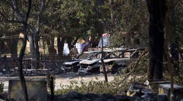 A policeman stands guard near torched vehicles where clashes between police and squatters claimed several lives in Mathura (AP)
