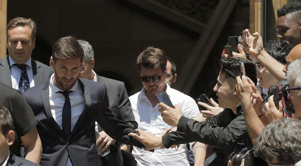 Lionel Messi, left, leaves the court in Barcelona (AP)