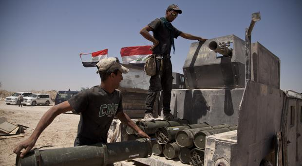 Iraqi forces load a truck with rockets to take to the front line in Fallujah (AP)