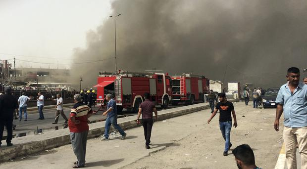 Iraqi security forces and civilians gather at the scene of a suicide car bomb attack in New Baghdad (AP)