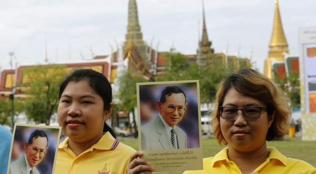 Visitors hold portraits of Thailand's King Bhumibol Adulyadej outside the Grand Palace during celebrations marking the 70th anniversary of his accession to the throne in Bangkok (AP)