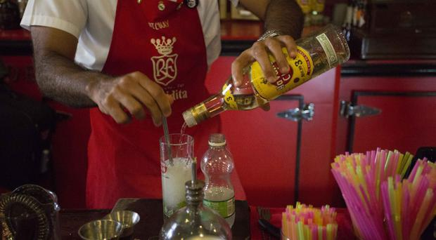 A bartender pours Cuban Havana Club rum for a mojito at the Floridita bar in Havana, as two drinks giants are escalating a 20-year fight to secure the rights to sell Havana Club rum in the United States.