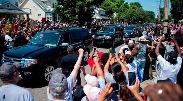 The hearse carrying boxing legend Muhammad Ali drives past his childhood home in Louisville, Kentucky, where mourners wait to pay respects yesterday
