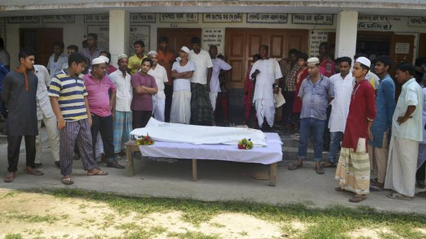 People surround the body of a Hindu monastery worker killed in Bangladesh (AP)