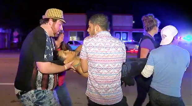 An injured person is escorted out of the Pulse nightclub in Florida, America