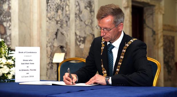 Sorrow: Belfast's Lord Mayor Brian Kingston signs the book of condolence for the 49 victims