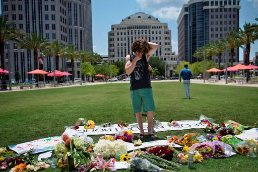 A man visits a makeshift memorial to the dead outside the Dr Phillips Center for the Performing Arts in Orlando