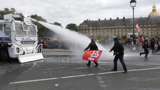 Police use a water cannon on protesters during demonstrations in Paris (AP)