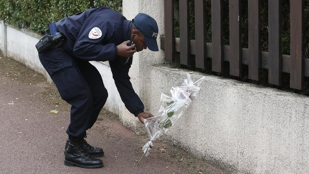 A French police officer lays flowers while paying tribute to his colleagues killed in a knife attack near their home in Magnanville (AP)