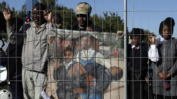 Members of the public watch the laying of wreaths at the Hector Pieterson Memorial in Soweto, South Africa (AP)