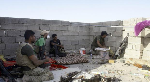 Iraqi soldiers observe the movements of Islamic State militants from a roof during fighting in Fallujah. (AP)