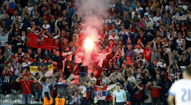 Russian fans light a flare during the Euro 2016 match between Russia and Slovakia, near Lille, France. (AP)