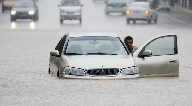 A motorist pushes his car through a flooded section of road in Jiujiang in southern China's Jiangxi province (AP)