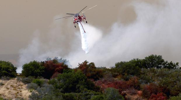 A helicopter joins the effort against a wildfire in Santa Barbara County (AP)