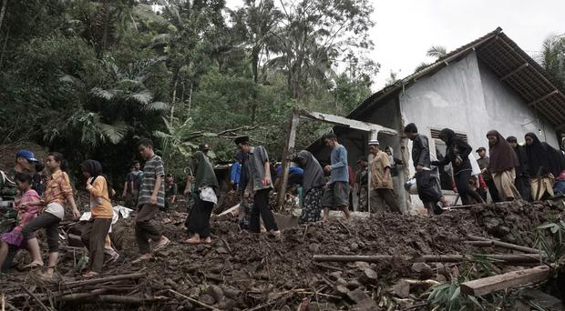 Villagers walk through the area affected by landslides in Banjarnegara, Central Java, Indonesia. (AP)