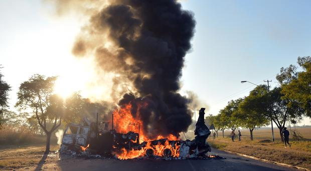 A vehicle burns during riots in Atteridgeville, Pretoria, South Africa (AP)