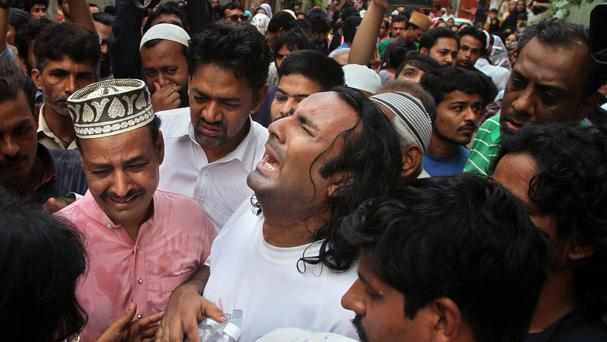 People comfort the brother, centre, of Sufi singer Amjad Sabri, who was killed in Karachi (AP)