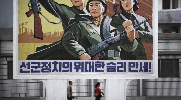 A North Korean man and woman walk under a mural with a message which reads