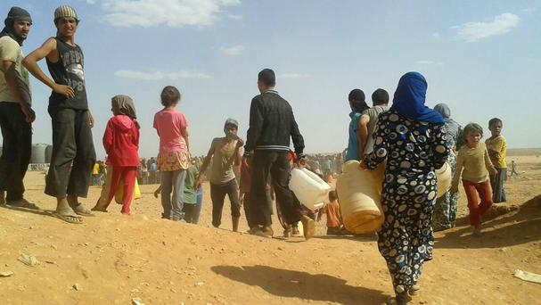 Syrian refugees gather for water at the Rukban refugee camp in Jordan's north-east border with Syria (AP)