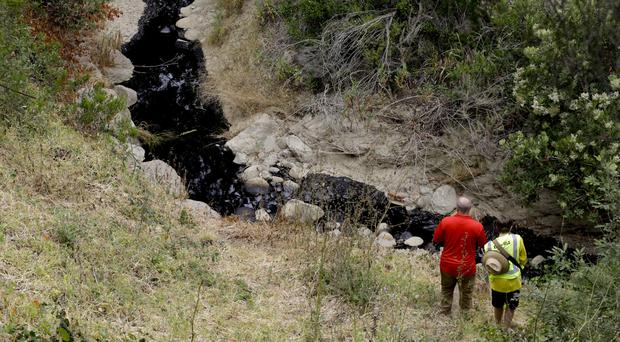 Professor Sean Anderson and his son, Gabriel, make their way down to the bottom of a ravine to study oil from a spill in Ventura (AP)