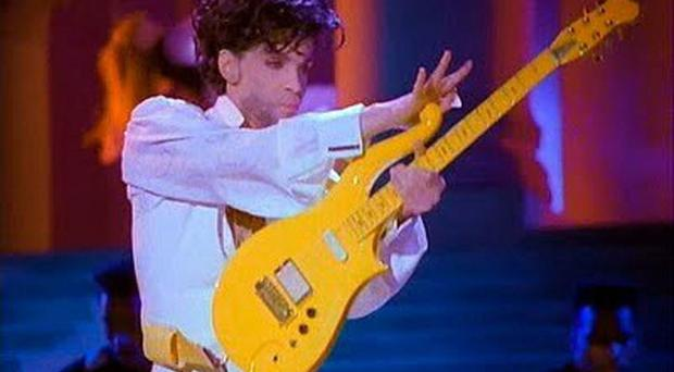 Prince playing his Yellow Cloud electric guitar, which has been sold at an auction in the US (Heritage Auctions/AP)
