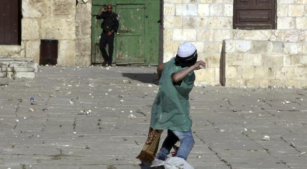 A Palestinian youth throws stones at an Israeli border policeman during clashes at Al-Aqsa Mosque compound in Jerusalem (AP)