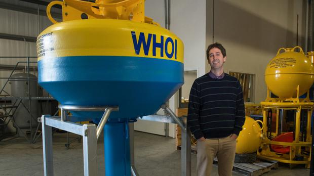 Dr Mark Baumgartner with the whale bouy that eavesdrops on whale songs (Wildlife Conservation Society/ AP)
