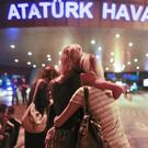 Evacuated passengers embrace at the entrance to Ataturk Airport (AP)