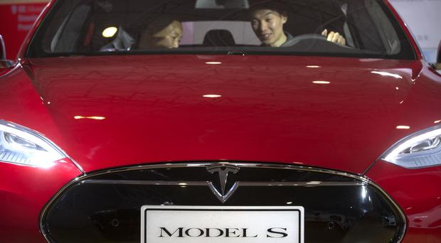 A man sits behind the wheel of a Tesla Model S electric car on display at the Beijing International Automotive Exhibition (AP)