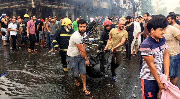 Iraqi firefighters and civilians carry the bodies of victims who were killed by a car bomb at a commercial area in Baghdad's Karada neighbourhood