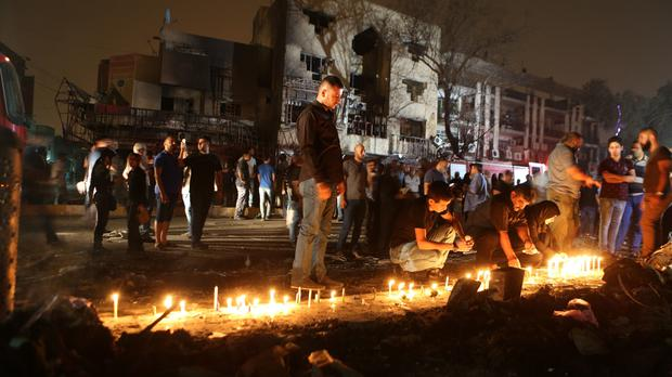 People light candles at the scene of the bomb attack in Karada (AP)