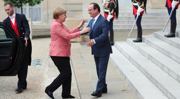 France's president Francois Hollande welcomes German chancellor Angela Merkel prior to the Balkans summit, at the Elysee Palace, in Paris (AP)