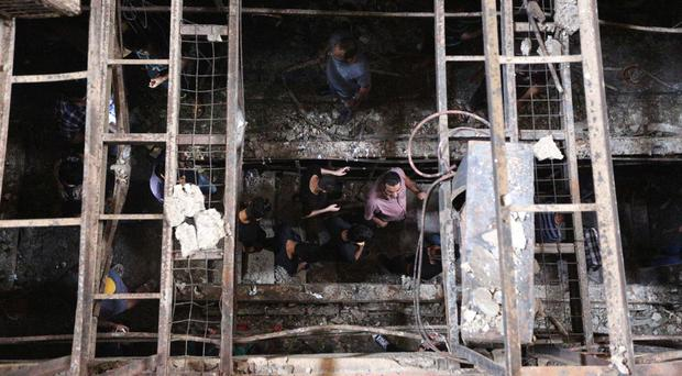 Rescuers look for victims after a suicide bomb attack in Karada, a busy shopping district in the centre of Baghdad, Iraq (AP)