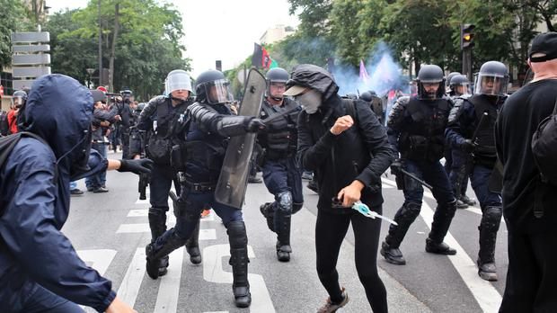 Riot police officers clash with protestors during a protest against the labour law bill in Paris (AP)