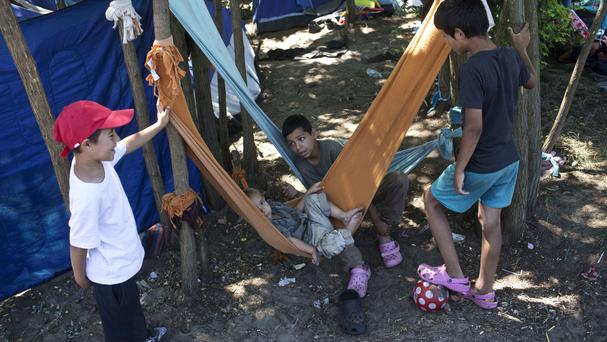 Children rest in hammocks at a makeshift camp for migrants and refugees situated metres away from the Serbian border with Hungary (AP)