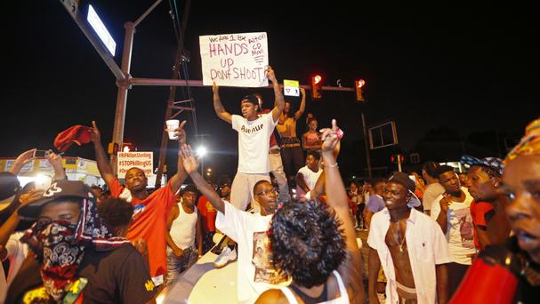 Protesters stand on cars in Baton Rouge after Alton Sterling was shot and killed by police (AP)
