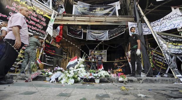 Iraqis gather at the scene of Sunday's massive truck bomb attack in Baghdad (AP)