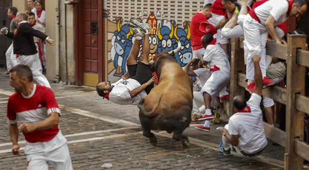 A reveller is gored by a bull during the San Fermin festival in Pamplona, Spain (AP)